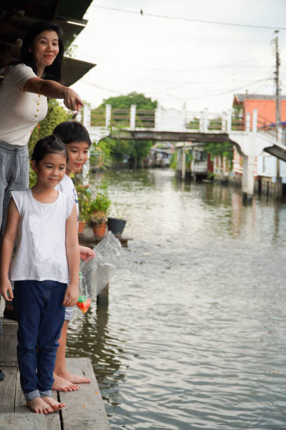 Mother With Kids Standing By Canal