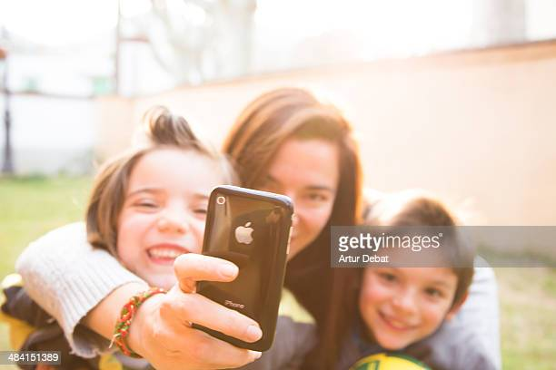 Mother with kids taking photos with smartphone in funny moment and sunset light