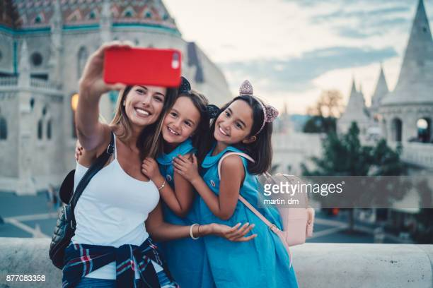 mother with kids taking selfie - royal palace budapest stock pictures, royalty-free photos & images