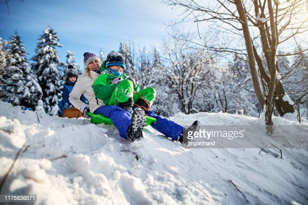 mother with kids tobogganing in winter - tobogganing stock pictures, royalty-free photos & images
