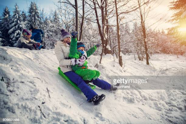 Mother with kids tobogganing in winter