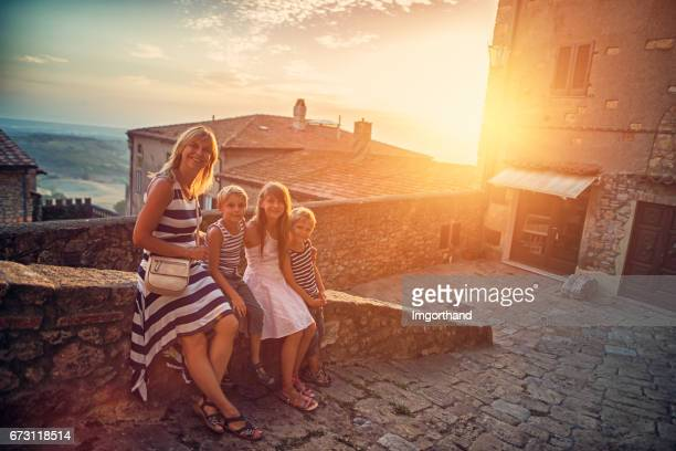 Mother with kids tourists visiting beautiful italian town in Tuscany