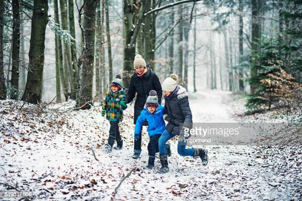 Mother with kids walking in beautiful winter forest
