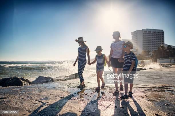 Madre con hijos caminando en la escollera