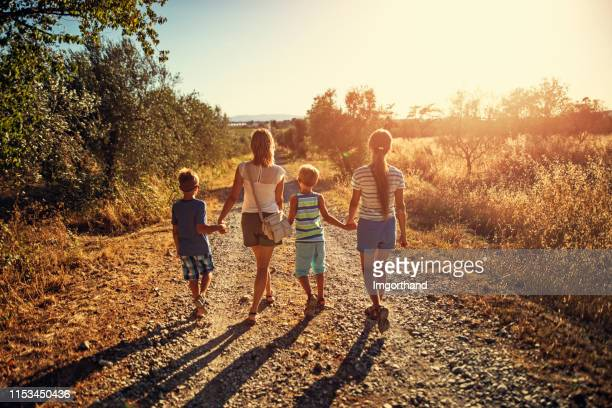moeder met kids walking on country road - alleenstaande moeder stockfoto's en -beelden