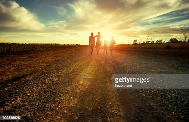 mother with kids walking on country road - speranza foto e immagini stock