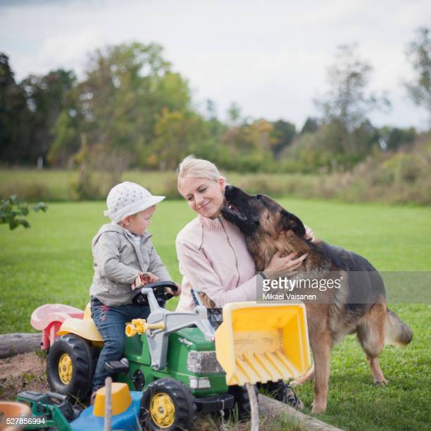 Mother with little daughter and dog in garden