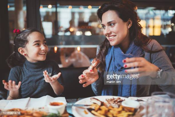 mother with little daughter eating dinner in restaurant - hungry stock pictures, royalty-free photos & images