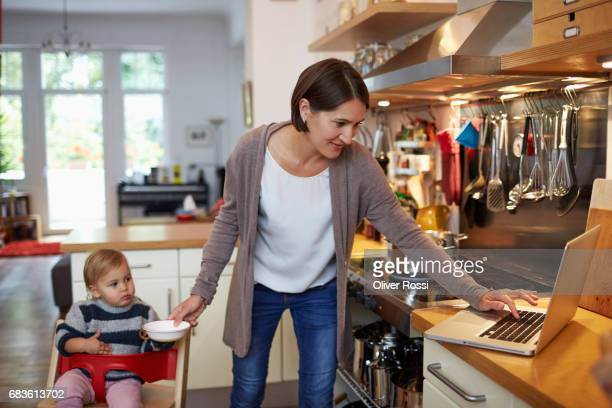 mother with little daughter using laptop in kitchen - cardigan photos et images de collection