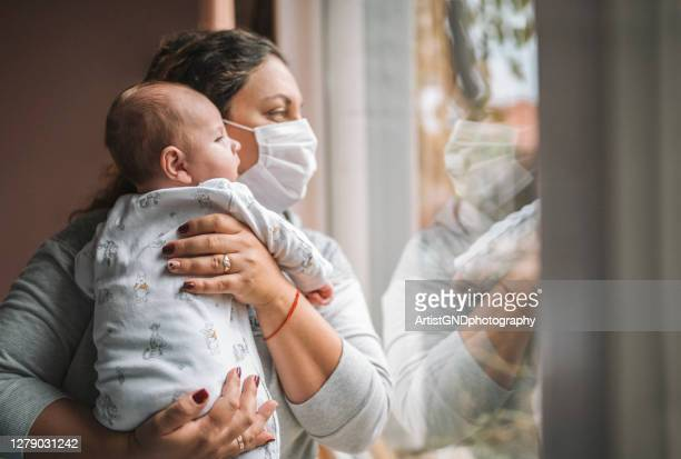 mother with protective mask and her newborn baby. - baby stock pictures, royalty-free photos & images