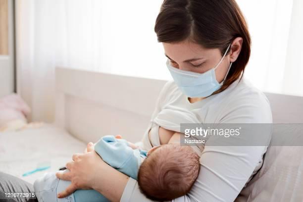 mutter mit schutzmaske stillt ihr baby auf einem bett sitzend - adult breastfeeding stock-fotos und bilder