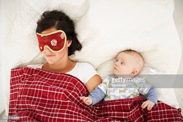 Mother with sleep mask and awake baby lying in bed