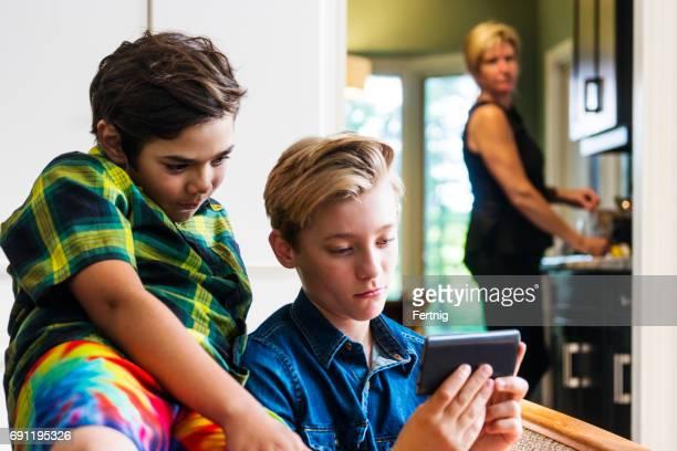 携帯電話でインターネットを使用して少年を見て彼女の顔に少し心配する表情で母