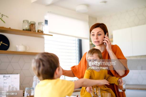 mother with small children indoors in kitchen in the morning at home, using telephone. - stress coronavirus stock pictures, royalty-free photos & images