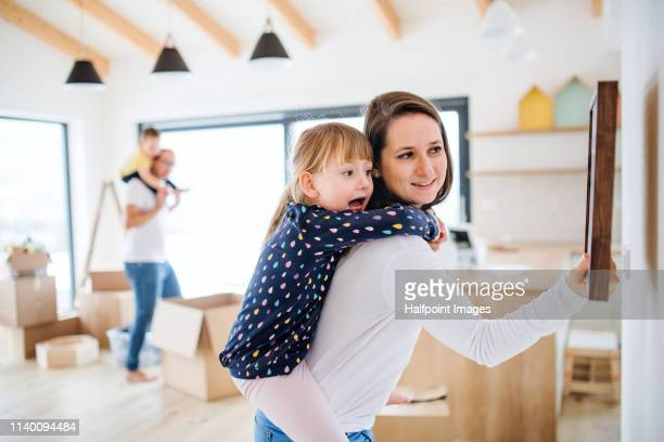 mother with small girl on her back moving in a new home, hanging up a picture on a wall. - hanging stock pictures, royalty-free photos & images