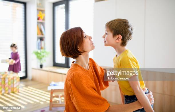 mother with small son indoors in the morning at home, getting dressed. - mother scolding stock pictures, royalty-free photos & images