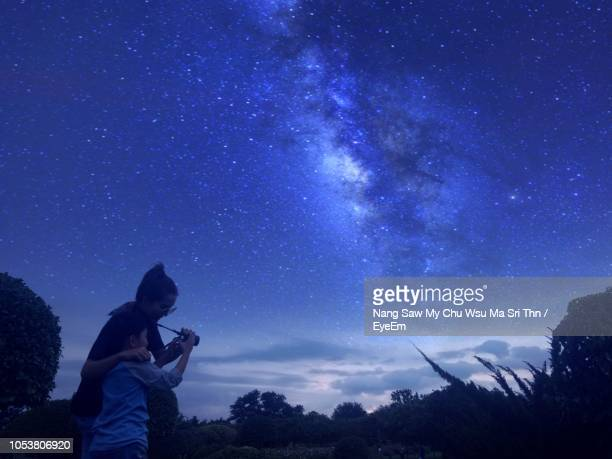 mother with son against star field - astronomy stock pictures, royalty-free photos & images