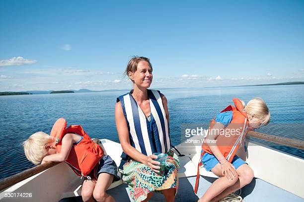 mother with son and daughter on boat - レクサンド ストックフォトと画像