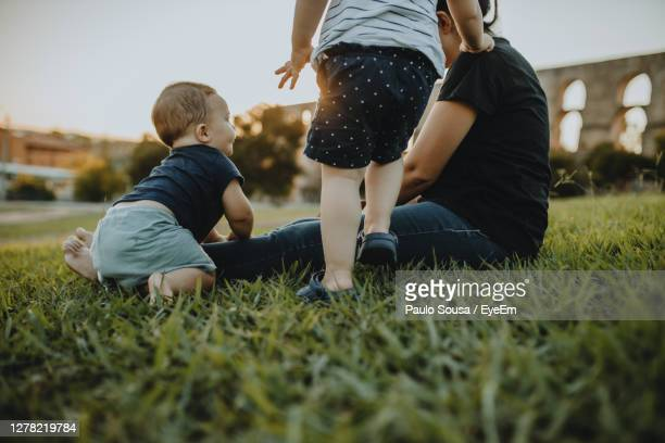 mother with son and daughter on grass - gras stock pictures, royalty-free photos & images