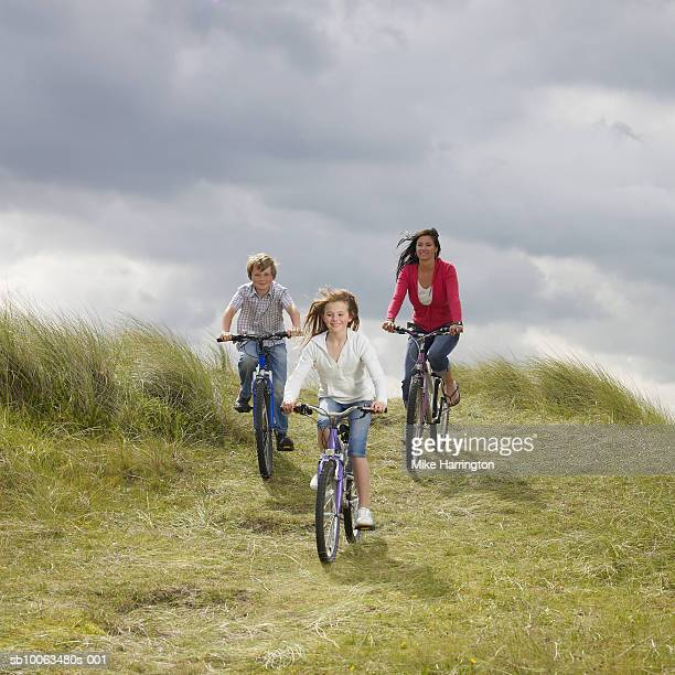 Mother with son and daughter (10-12) riding bikes on meadow