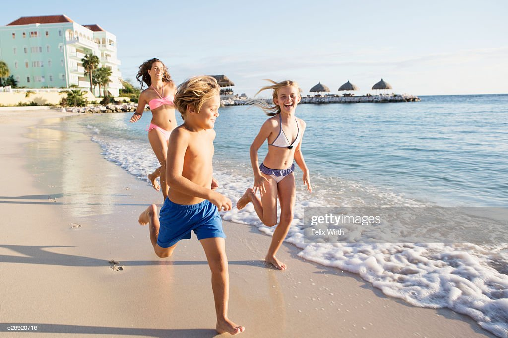Mother with son (8-9) and daughter (10-11) running on beach : Foto de stock