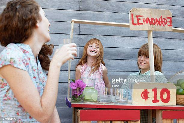 Mother With Son and Daughter Selling Lemonade on Stand