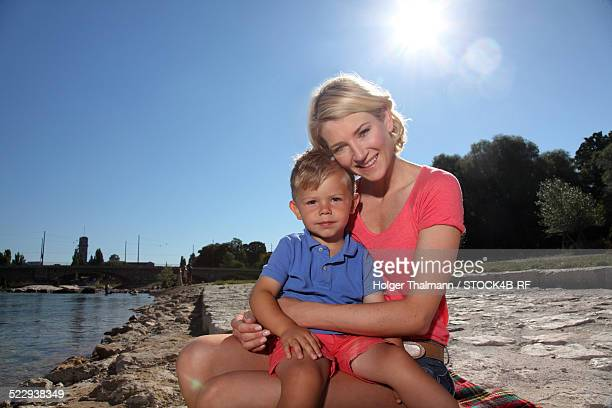 """""""mother with son at river isar, munich, germany"""" - mom sits on sons lap stock pictures, royalty-free photos & images"""