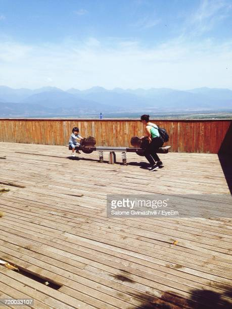 Mother With Son Enjoying Seesaw Against Sky On Sunny Day