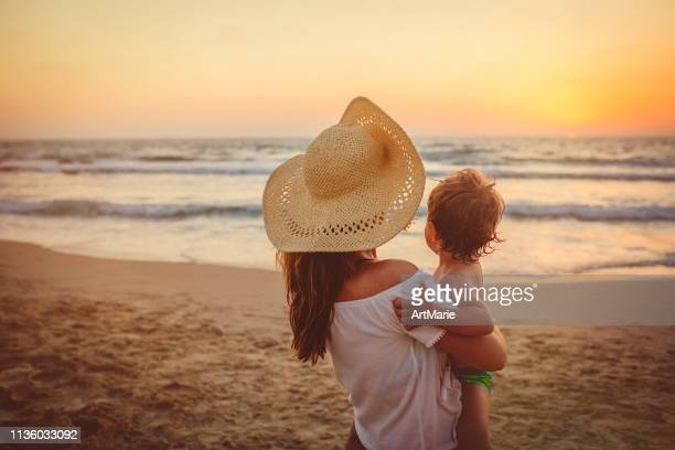 mother with son enjoying sunset on the beach - israeli woman stock pictures, royalty-free photos & images