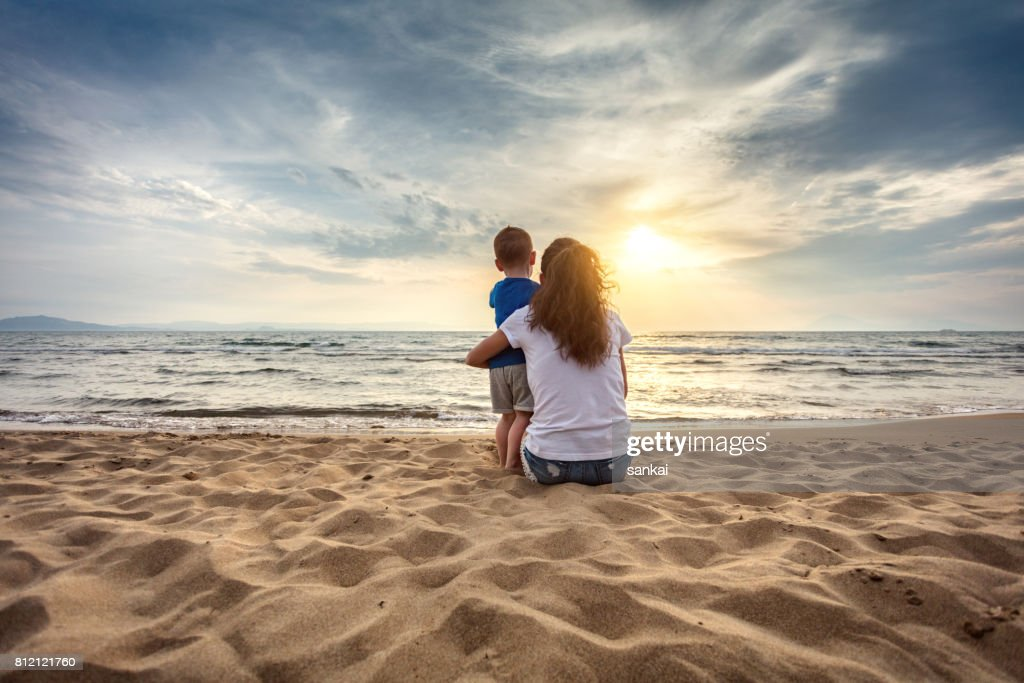 Mother with son enjoying sunset on the beach : Stock Photo
