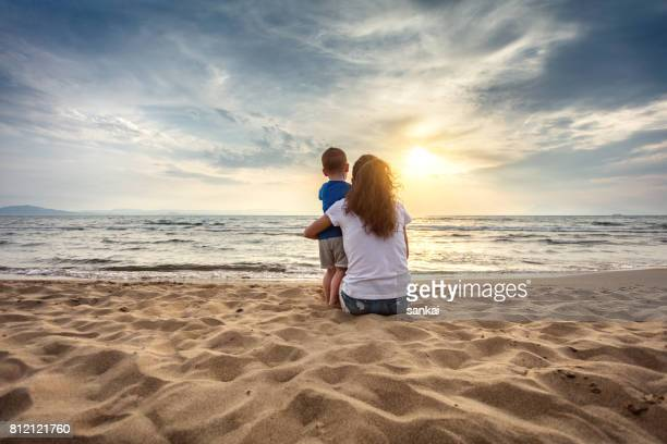 mother with son enjoying sunset on the beach - mother and son stock photos and pictures
