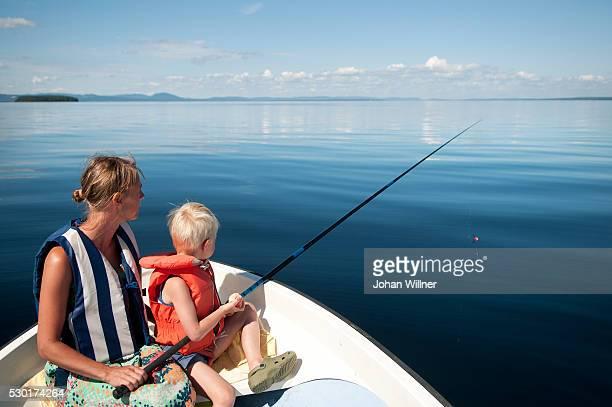 mother with son fishing on boat - レクサンド ストックフォトと画像