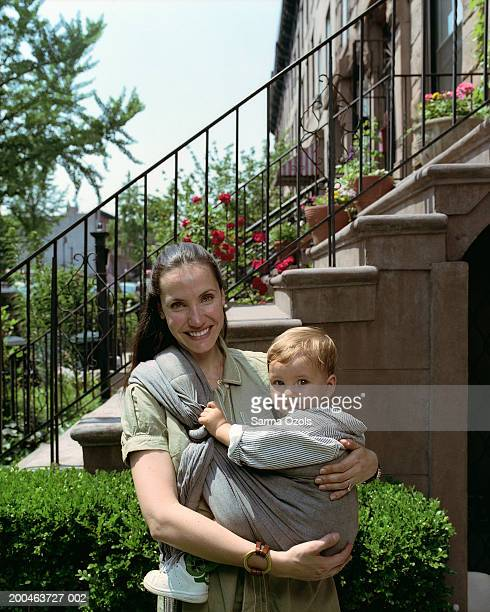 Mother with son (15-17 months) in baby carrier, smiling, portrait