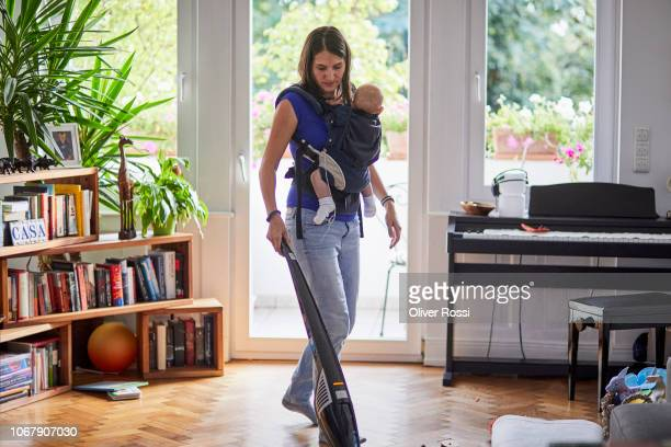mother with son in baby carrier vacuum cleaning at home - hausmann oder hausfrau stock-fotos und bilder