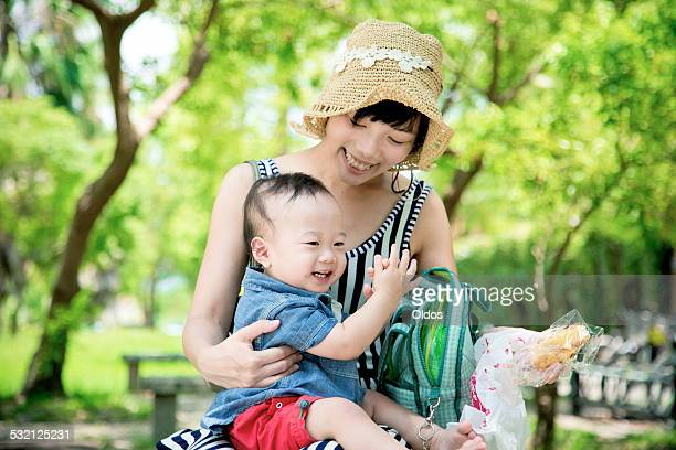 Mother with son (6-11 months) in park