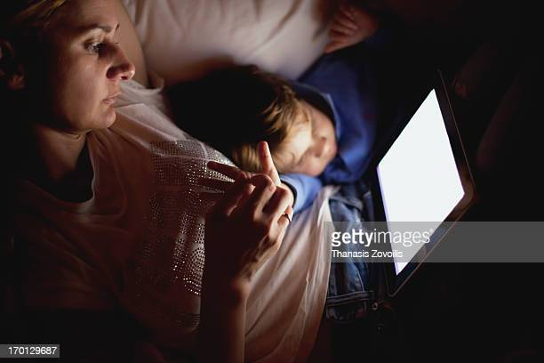 Mother with son looking at a tablet in the dark