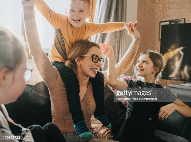 mother with son on her shoulders, is surrounded by her happy children - home interior stock pictures, royalty-free photos & images