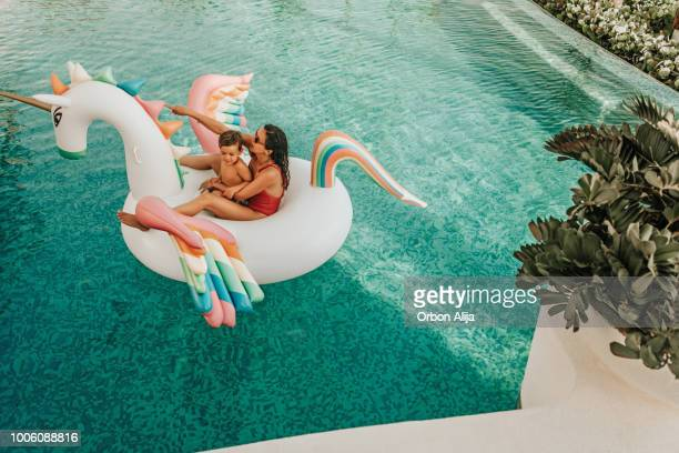 mother with son on inflatable unicorn - unicorn stock pictures, royalty-free photos & images