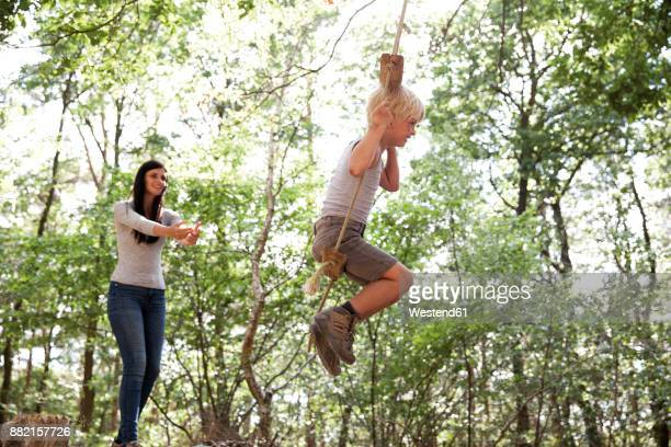 Mother with son on swing in forest