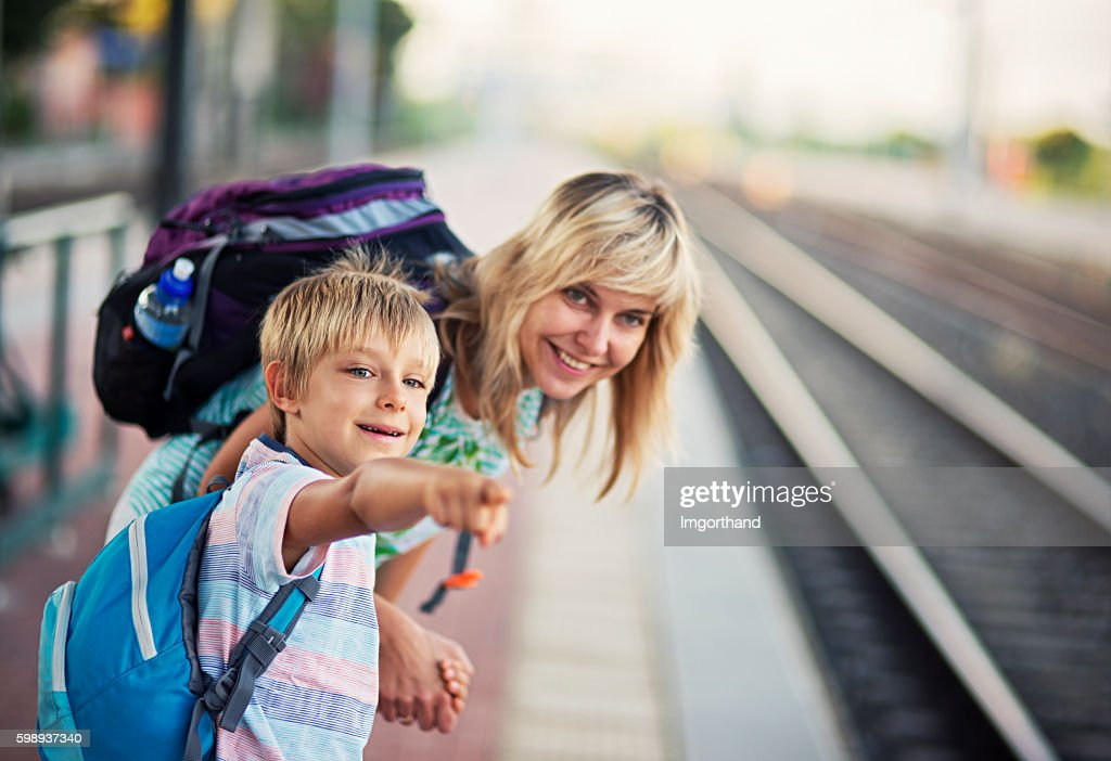 Mother with son on train station watching the incoming train : Stock-Foto