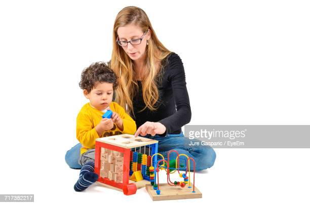 Mother With Son Playing Beads Wire Maze Game On White Background