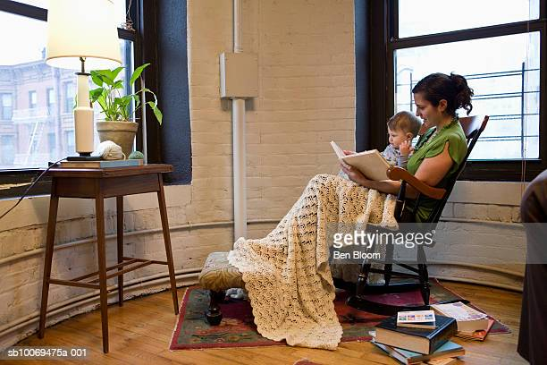 Mother with son (12-17 months) sitting on chair reading book, side view