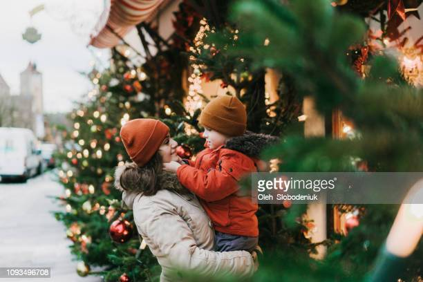 mother with son  standing near christmas tree in rothenburg - christmas family stock pictures, royalty-free photos & images