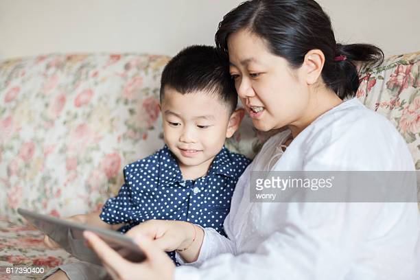 Mother with son using digital tablet