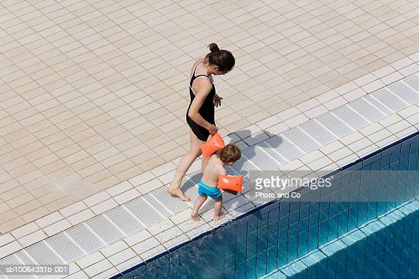 Mother with son (21-24 months) walking by pool, elevated view