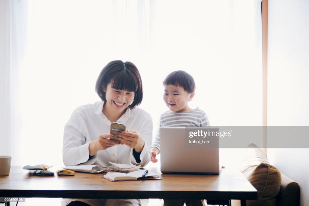 Mother with son working at home : Stock Photo