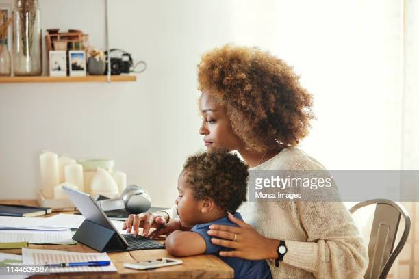 mother with son working on digital tablet at home - working from home stock pictures, royalty-free photos & images