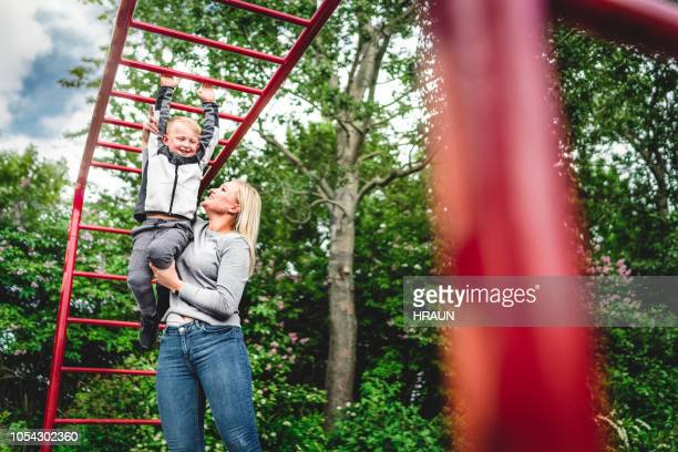 mother with stoma bag helping son on monkey bars at public park - colorectal cancer stock photos and pictures
