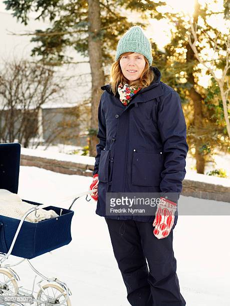 Mother with stroller in park at winter