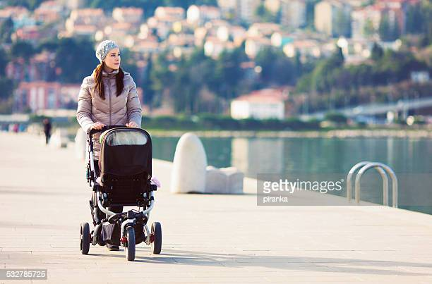 Mother with stroller walking by the sea